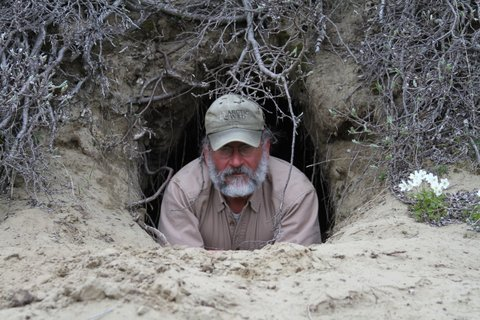 Jeff trying out a grizzly den he found during yellow-billed loon work in the Alaskan Arctic tundra © Jim Paruk